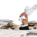 An unorganized pile of paperwork and files, with the hand of a businessman clutching paper sticking out of the clutter.